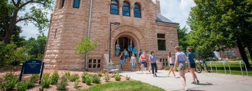 A campus tour group heading out of Scoville Hall on a sunny day