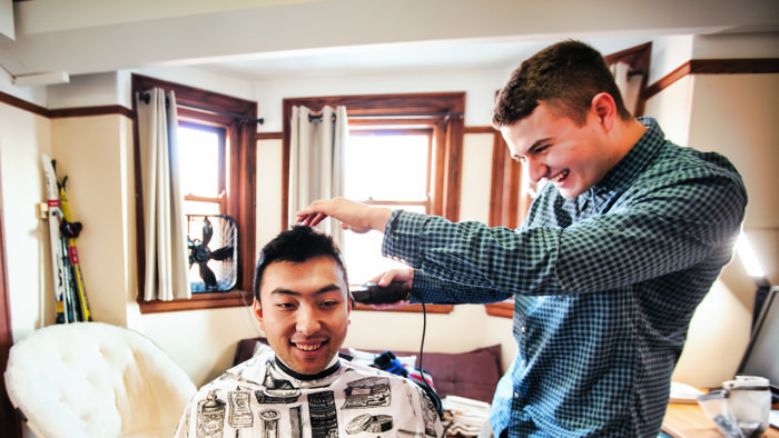 Junior Simon Orlovsky cuts a fellow student's hair in their dorm room