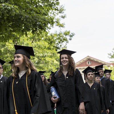 Students in caps and gowns process towards commencement