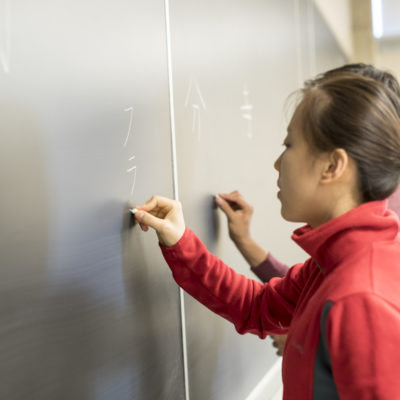 A student writes at the board in a Japanese class