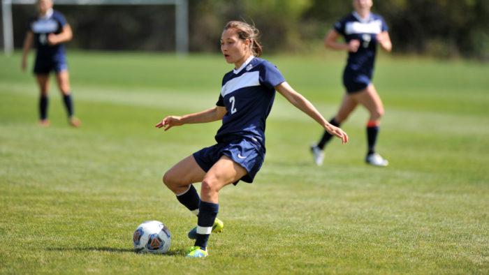 A Carleton varsity women's soccer player kicks the ball