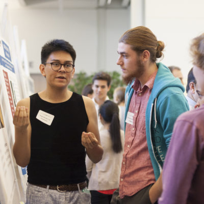<p>Students have a conversation during a poster session for student research and externship positions</p>
