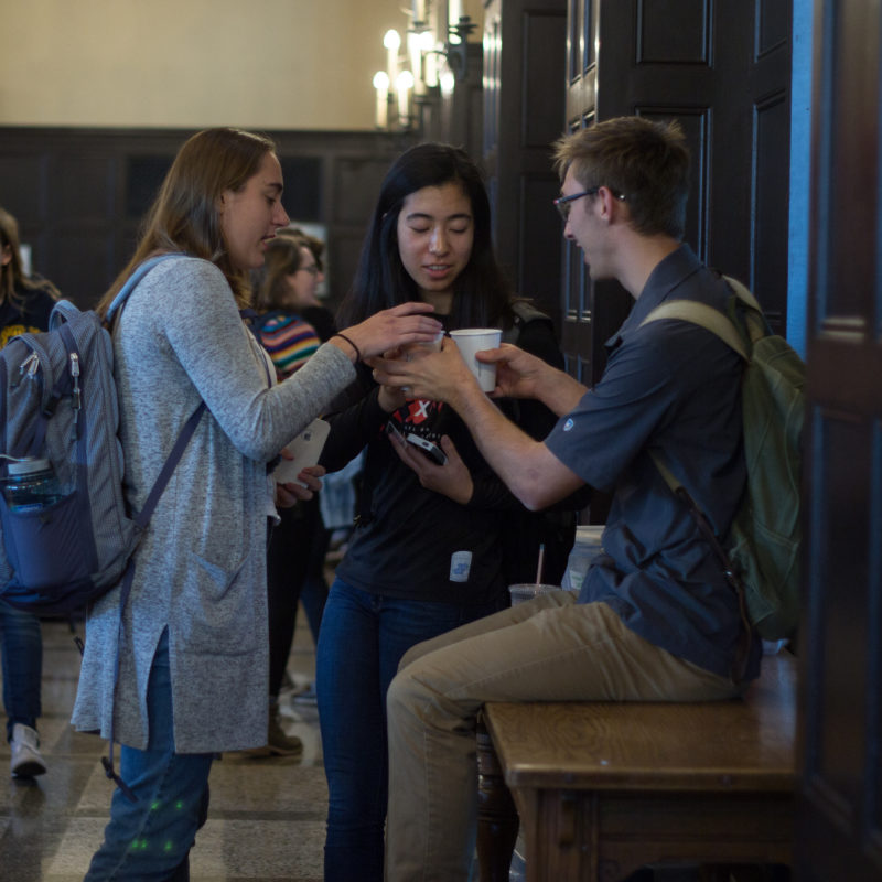 Three students chat in Carleton's wood-paneled Great Hall