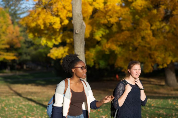 Two students have a conversation on a crisp fall day