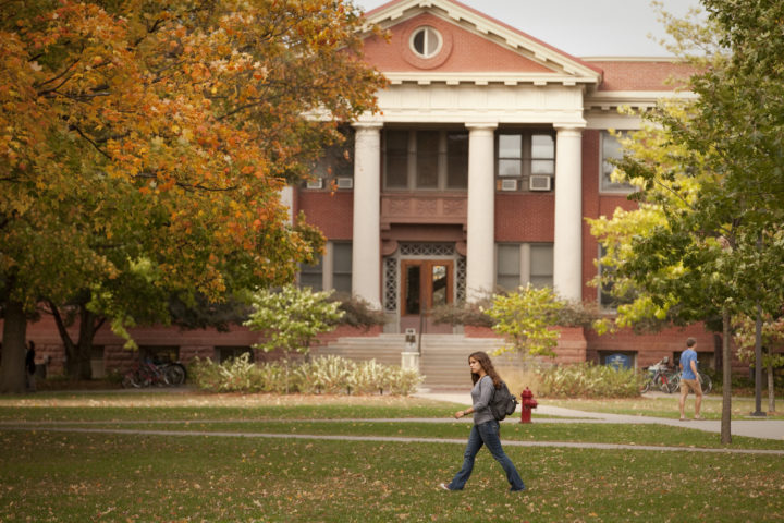 A student walks in front of Laird Hall, a large brick building, on a fall day