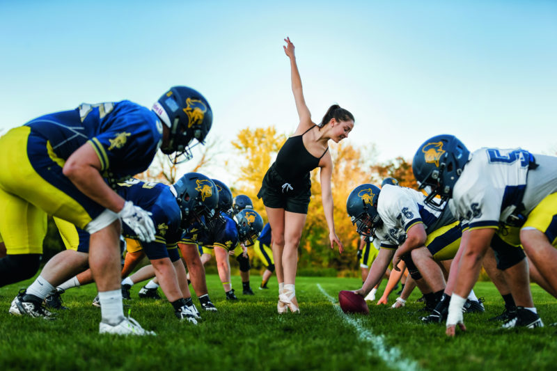 A ballerina standing en pointe in the middle of a football line of scrimmage
