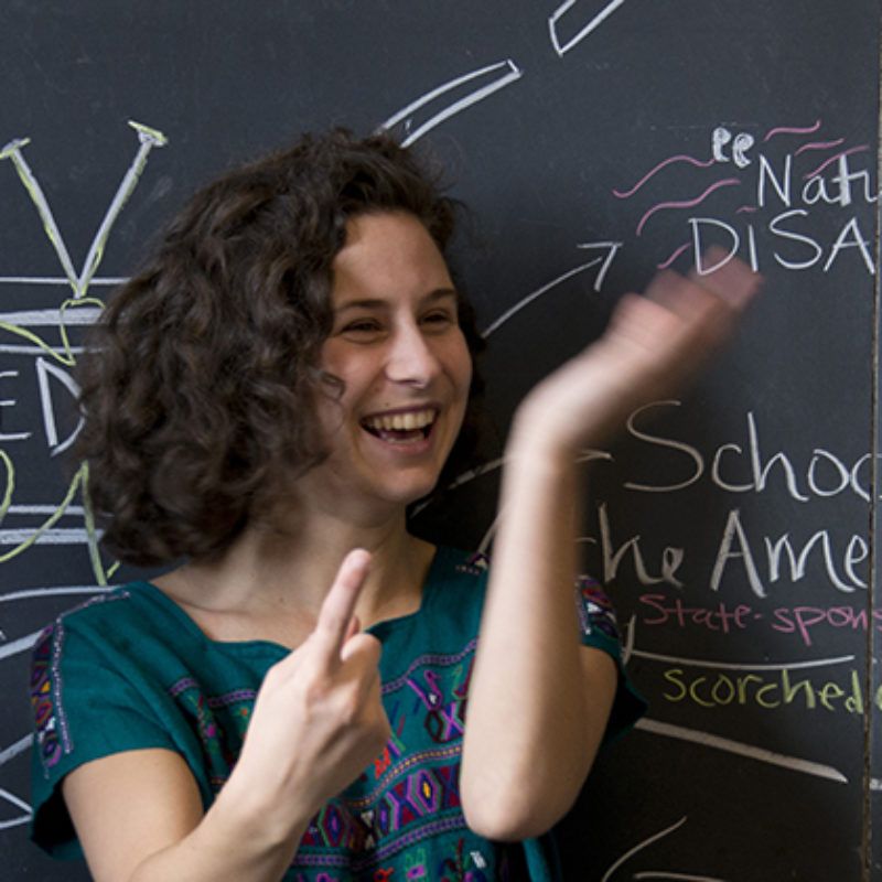 Two students gesture and laugh in front of a chalkboard.
