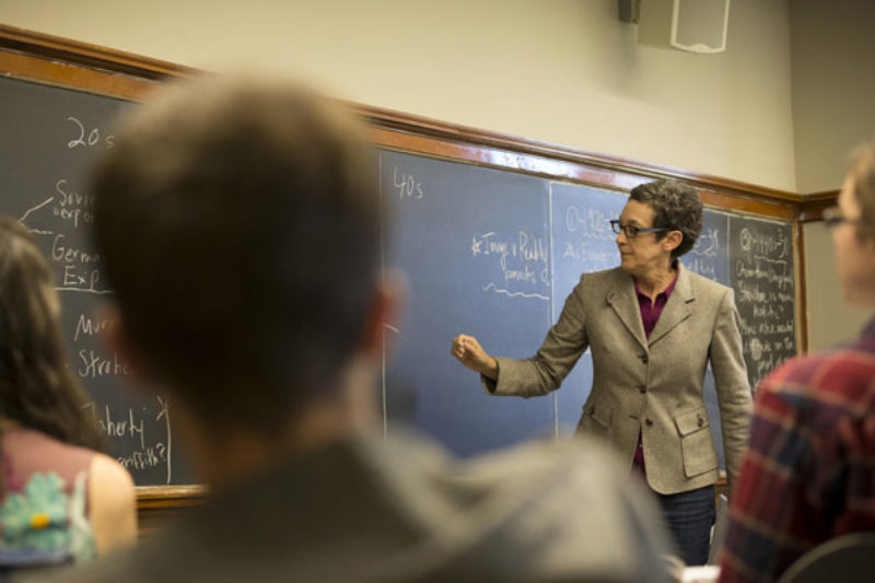 A professor writes on a blackboard in front of a class of students