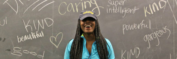 "Student smiling in front of blackboard with words like ""kind,"" ""caring,"" and ""powerful"" written on it"
